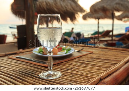 Natural light photo with shallow DOF of romantic beach evening on the sunset with glass of water and dinner horizontal view 1