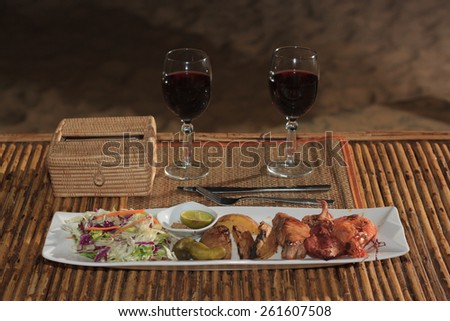 Natural light photo with shallow DOF of seafood mix barbecue with salad and two glasses of wine on plate on bamboo table - stock photo