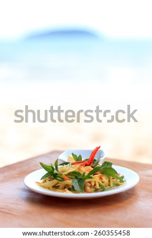 Natural light photo with shallow DOF of spicy green mango salad on a wooden table with a sea view on the background - stock photo