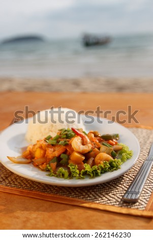 Natural light photo with shallow DOF of stewed seafood with vegetables, steamed rice with sea view background - stock photo