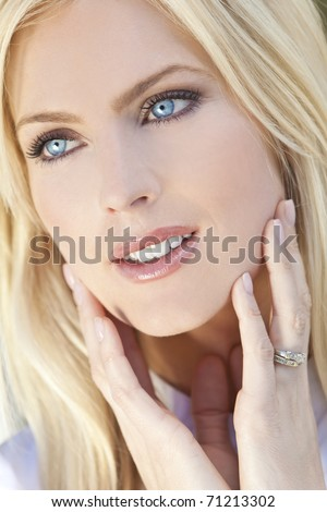Natural light portrait of a beautiful blond woman with blue eyes - stock photo