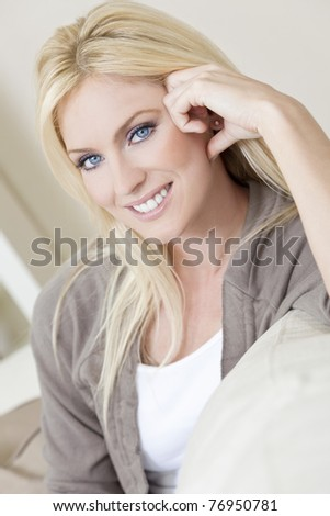 Natural light portrait of a beautiful blond woman with blue eyes resting on her sofa at home - stock photo