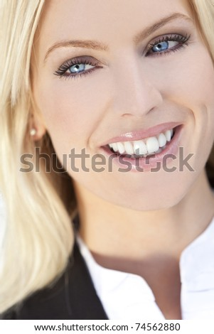Natural light portrait of a beautiful smiling blond woman with blue eyes - stock photo