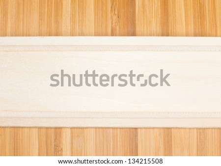 Natural light wood banner formed from the partial view of a wooden kitchen utensil place horizantally over darker wood with a definite woodgrain pattern - stock photo
