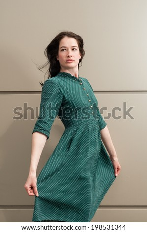 Natural look girl wearing a green dress with white dots posing outdoor while wind is blowing - stock photo