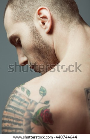 Natural male beauty. Close up portrait of handsome charismatic man posing over gray background. Tattoo on shoulder. Close up. Studio shot