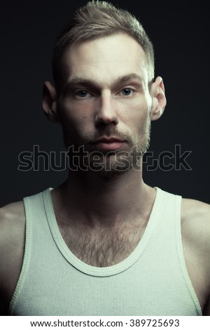 Natural male beauty concept. Close up portrait of handsome charismatic man posing over gray background in white sleeveless underwear. Stylish modern haircut. Studio shot