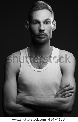 Natural male beauty concept. Portrait of handsome charismatic man posing over dark gray background in white sleeveless shirt. Stylish modern haircut. Monochrome studio shot