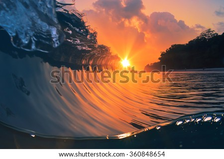 Natural marine design postcard. Beautiful colored breaking surfing ocean wave rolling down at sunset time. - stock photo