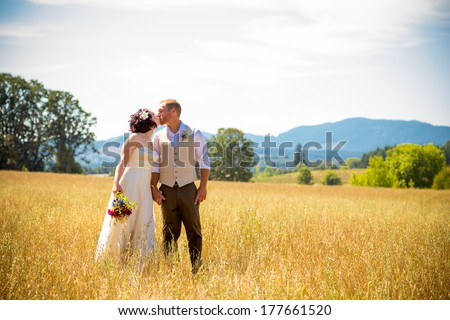 Natural meadow or field plays host for this portrait of the bride and groom on their wedding day after just getting married during their ceremony. - stock photo