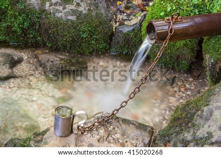 Natural mountain stream in the woods. Mug on iron chains. - stock photo