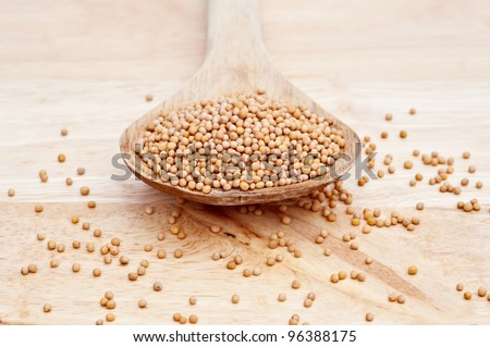 Natural mustard seeds on a wooden serving spoon on wooden board with selective focus