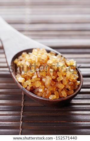 Natural not purifed brown sugar in wood spoon