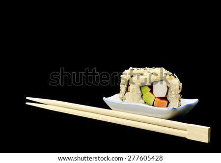 Natural organic brown rice Japanese sushi and chopsticks isolated on black background - stock photo