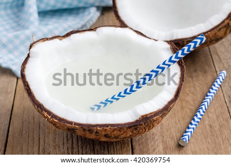 Natural organic coconut water in cracked coconut on wooden table - stock photo