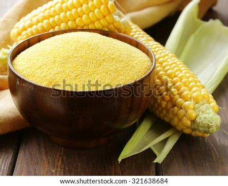 Natural organic corn grits and cobs on the wooden table - stock photo