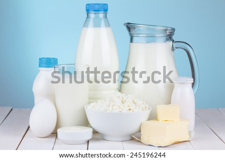 Natural organic dairy products, milk, cottage cheese, eggs, butter, yoghurt, butter and sour cream on white wooden bale and blue background still life - stock photo