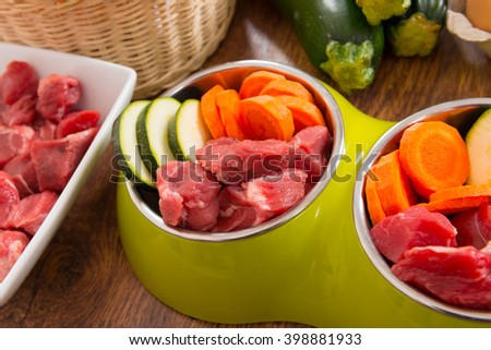 Natural, organic dog's food in a bowl with ingredients zucchini, carrot and raw meat