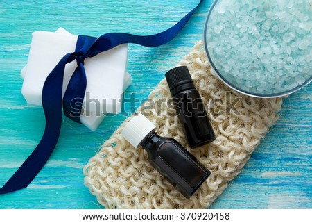 natural organic soap bottles essential oil and sea salt herbal bath  on a blue wooden table, Spa - stock photo