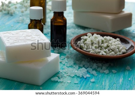 natural organic soap bottles essential oil and sea salt   on a blue wooden table, Spa with flowers - stock photo
