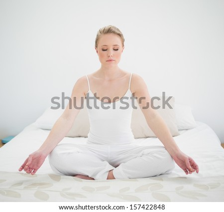 Natural peaceful blonde meditating on bed in bright bedroom - stock photo