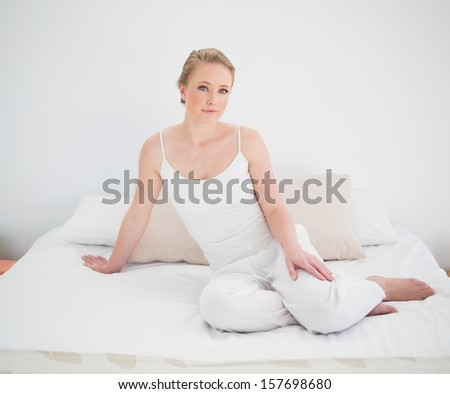 Natural peaceful blonde sitting on bed in bright bedroom