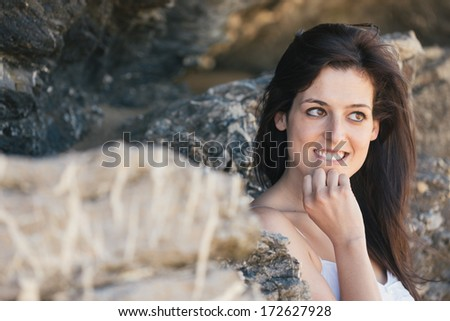 Natural pensive woman biting her lip and smiling. Expressive female face. - stock photo