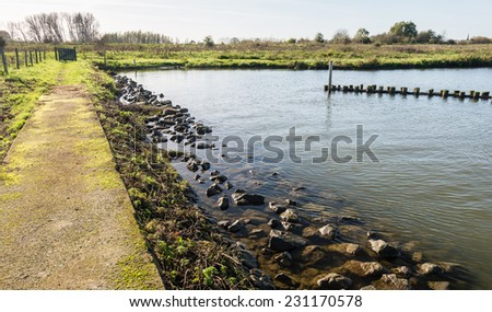 Natural pond with a concrete walkway and a breakwater constructed of wooden poles. - stock photo