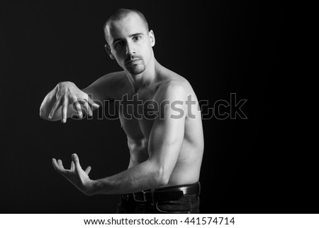 Natural portrait of guy in studio over black background