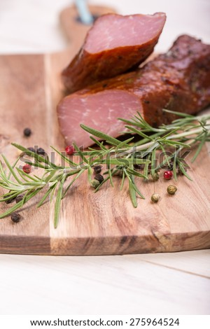 Natural prepared slow food. Smoked pork sirloin with herbs and spices on wooden board. Traditional Polish cold meats - stock photo