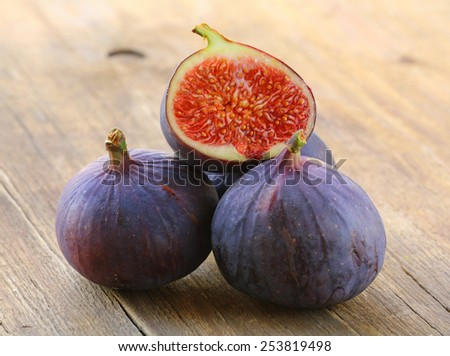 natural purple ripe figs on a wooden table - stock photo