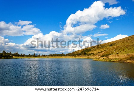 natural reflections on a lake and beautiful clouds. Ukraine - stock photo