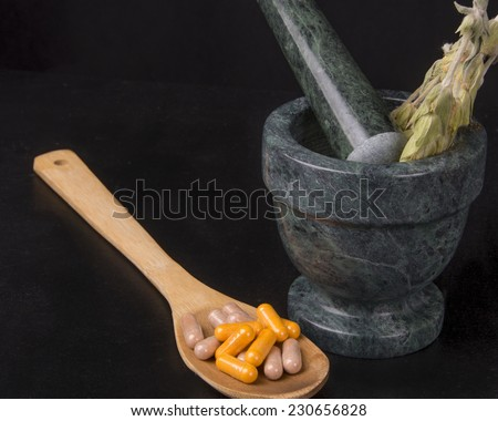 Natural remedies on a black background/Natural Remedies/Stalks of fresh herb and bolls illustrate alternative holistic medicine - stock photo