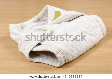 Natural reusable cloth diaper isolated on the bright wooden background