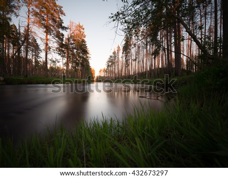 Natural river with surrounding trees photographed with long exposure