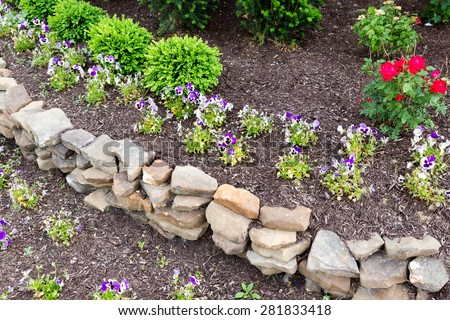 Natural Rock Retaining Wall In A Garden With Rough Rocks And Stones  Arranged In A Curve