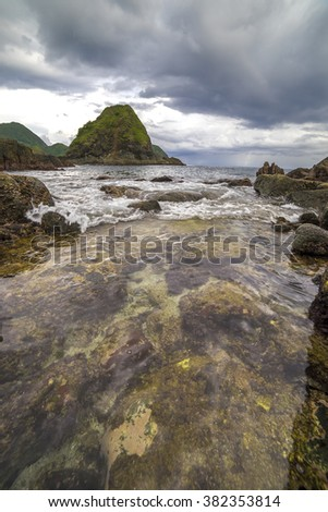 Natural rock with strong water wave and cloudy sunset background at Pantai Semeti Lombok, Indonesia
