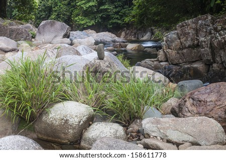 Natural rocks along the stream in the tropical forest. - stock photo