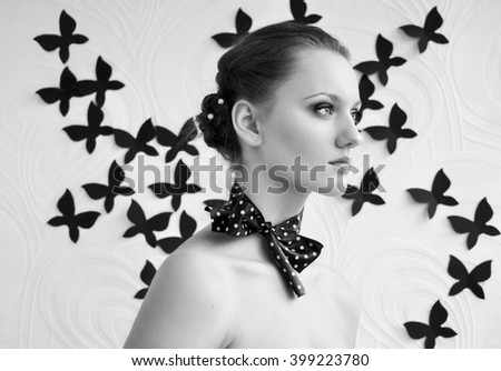 Natural romantic portrait of beautiful young girl with cute bow on neck, model face with clean skin. Standing on background with flying handmade black paper butterflies. Black and white - stock photo