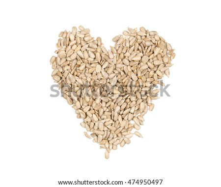Natural shelled sunflower seeds heart shaped heap over white background