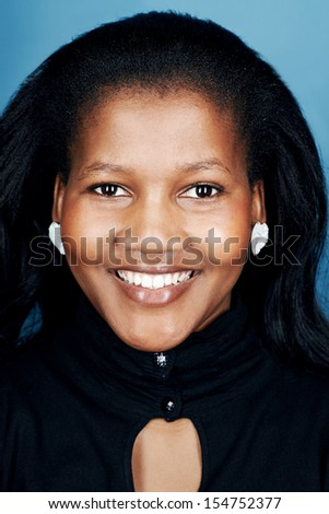 natural smiling black african portrait of real woman on blue background