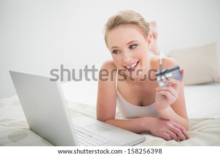 Natural smiling blonde holding credit card and looking at laptop in bright bedroom - stock photo