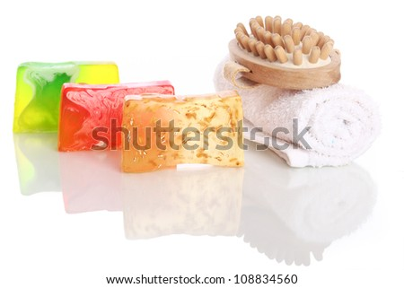 Natural soap with white towel and wooden brush over white background - stock photo