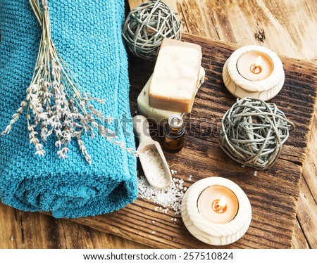 Natural Spa and Wellness Product on Wooden Background with Burning Candles, Towel,Homemade Soap and Lavender Bouquet - stock photo