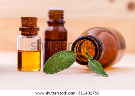 Natural Spa Ingredients sage essential oil for aromatherapy with sage leaf on wooden background. - stock photo