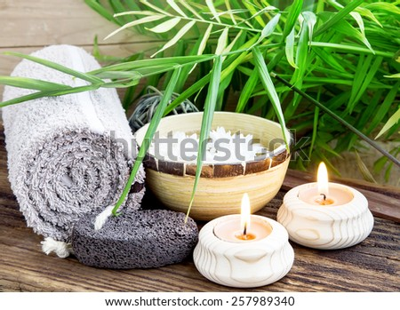 Natural Spa Setting with Green Leaves and Burning Candles, Towel and Pumice, Bamboo Bowl with Water on Wooden Background - stock photo