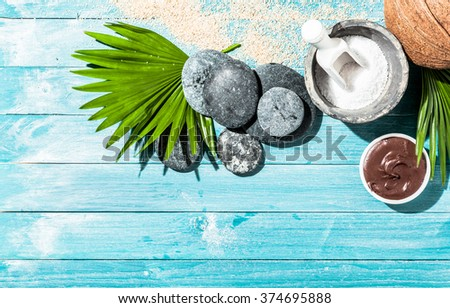 Natural spa therapy items as background with various sponges, sea salt, palm leaf and stones over blue wooden panels - stock photo