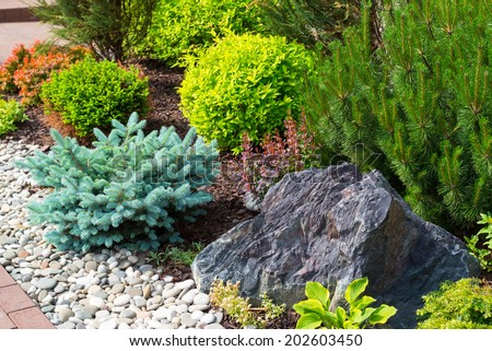 Natural stone landscaping in home garden - stock photo
