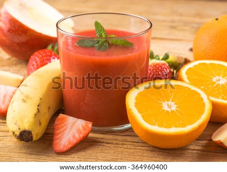 natural strawberry smoothie surrounded by fruit on wooden base