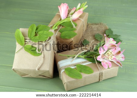 Natural style handcrafted gift boxes with fresh plants and rustic twine, on wooden  - stock photo